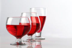 Three Red Wine Glasses on White Reflective Background Royalty Free Stock Image
