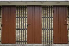 Three Red Wooden Doors in Yellow Brick Wall Royalty Free Stock Photos