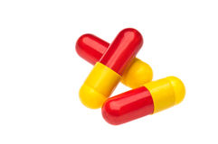 Three red yellow capsules over white Stock Photography