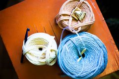 Reel thread. Three reel thread with knitting hook on the wooden orange desk stock photography