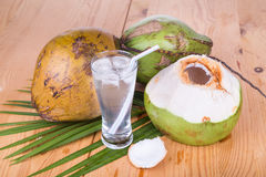 Three refreshing green coconut fruit juice in glass on wooden ta Stock Image