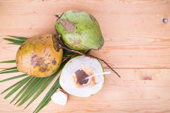 Three refreshing green organic coconut fruit juice on wooden tab Stock Photo