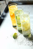 Three refreshing tangy citrus summer cocktails. Served in tall glasses flavoured with lemon, lime and orange and chilled on ice, high angle view in a receding Stock Photos