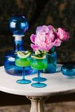 Three refreshing tequila cocktails on a marble surface. Beautifully styled tequila cocktails in vintage blue glassware on a marble table stock images