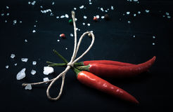 Three related twine red hot peppers on a blackboard. With space Royalty Free Stock Images