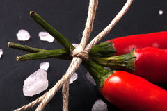 Three related twine red hot peppers on a blackboard tinted.  Royalty Free Stock Photos