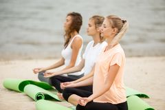 Three relaxed young girls sit in the lotus positions with closing eyes doing yoga on mats on sandy beach on a warm day royalty free stock photo