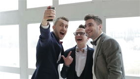 Three representative attractive handsome men in suits and bow ties making selfie near the large window. Slow motion. Three representative attractive handsome stock video footage