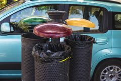 Three retro-style wastebaskets to recycle different materials. With a ashtray on a street in Cefalu in Sicily, Italy Stock Images