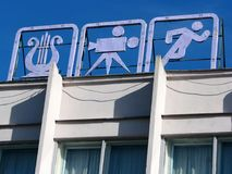 Three retro symbols of sport and culture on urban building roof. Old soviet times three retro white metal sign symbols of sport and culture on simple urban stock photos