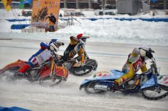 Three riders ice speedway compete on corner entry Royalty Free Stock Images
