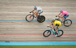 Three Riders on Velodrome Track. Blaine, MN - June 8: Men's Velodrome Cycling: 20 K Points/Madison race hang-sling riders pack on June 8, 2008 Royalty Free Stock Photos