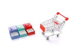 Three rings in gift boxes with empty shopping cart royalty free stock image