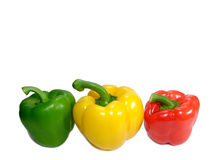 Three ripe bell peppers, green and yellow and red, with stem isolated on white background Royalty Free Stock Photo