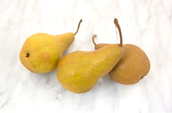 Three ripe bosc pears on cutting board Stock Image