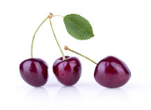 Three ripe cherries with leaves on a white background Royalty Free Stock Photography