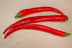 Three ripe chili pepper on the board Royalty Free Stock Image