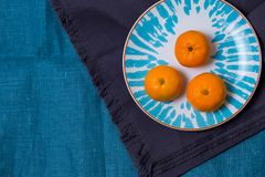 Three ripe delicious juicy Mandarin lie in a bright white with a blue plate patterns on fabric cloth kitchen towel stock images