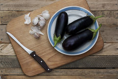 Three ripe eggplants on the plate. With knife and garlic on rustic weathered wooden table Stock Images