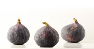 Three ripe fig fruit on a light background with reflection Stock Photo