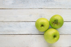 Three ripe green apples. Natural fruit with leaves on a white wooden table Stock Images
