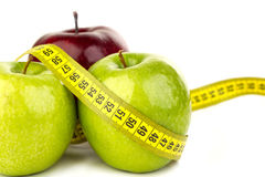 Three ripe juicy apples and tape measure. Three ripe juicy apples, almonds, and tape measure on a white background Royalty Free Stock Images