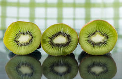 Three ripe kiwi slices sitting on a reflective surface. Royalty Free Stock Images