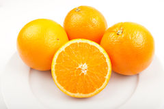 Three ripe oranges and one sliced. On white background Royalty Free Stock Photo
