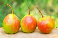 Three ripe organic pears on wooden board, blurred background, selective focus. Stock Photo