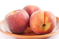 Three ripe peach. On a ceramic plate Royalty Free Stock Image
