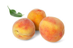 Three ripe peach with a leaf Stock Photography