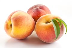 Three ripe peach with leaves Stock Images