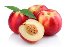 Three ripe peach (nectarine) fruits with slices isolated. On white Stock Photos