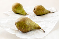 Three ripe pears on crumpled card Royalty Free Stock Image