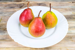 Three ripe pears in white plate on rustic wooden table Royalty Free Stock Photo