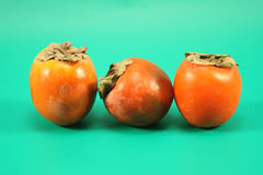 Three ripe persimmons Royalty Free Stock Photography