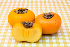Three ripe persimmons on table Royalty Free Stock Photos