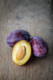 Three ripe plums with leaves Royalty Free Stock Images