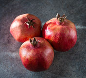 Three ripe pomegranate. On a gray background Royalty Free Stock Images