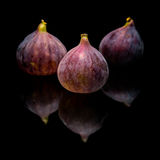 Three ripe purple fig fruits. Isolated on black background, with reflection stock photo