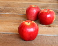 Three ripe red apples. On a rustic wooden background with selective focus on the apple in front Stock Photos