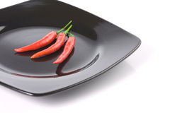 Three ripe red chili pepper on a black dish. Over white background royalty free stock image