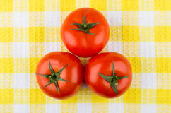Three ripe red tomatoes on plaid napkin Royalty Free Stock Photo