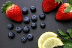 Strawberries, lemon slices, mint leaves and blueberries on black slate background. Three ripe strawberries with some mint leaves, Lemon slices and group of royalty free stock photo