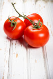 Three ripe tomatoes. Ripe tomatoes on old table from boards Stock Photography