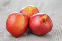 Three ripe whole nectarines Stock Photos