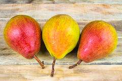 Three ripe yellow and red pears on rustic wooden background Stock Photography