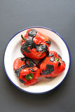 Three roasted red pepper on an enamel plate Royalty Free Stock Images