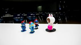 Three robotic guards are assembled with blue helmets with red horns to bring down a white bear with a pink candy trespassing onsta royalty free stock photos
