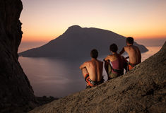 Three rock climbers having rest at sunset. Three rock climbers wearing safety harness having rest at sunset. With picturesque view of Telendos Island in front Royalty Free Stock Photos